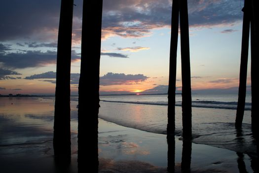 Silhouette pier supports against a sunrise on the beach
