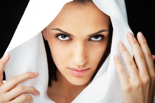 Close-up of beautiful woman holding white veil over  head, looking at camera