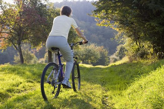Woman on a mountainbike at sunset in autumn