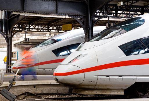 Two modern express trains waiting at platforms on station
