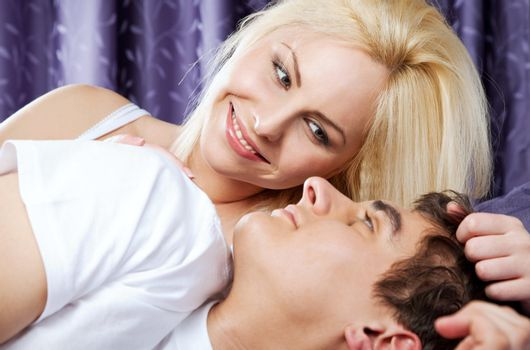 happy young couple in bed awaken by the sun