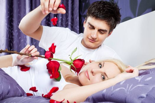 romantic couple in bed, female holding red rose, male releases  petals