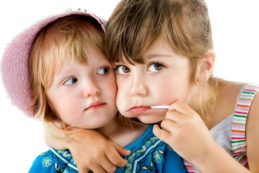 Close-up of two sweet little girls, one with lollipop in mouth hugging
