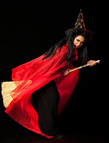 witch with a red cloak, hat and a broom between her legs