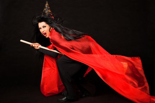 Female in witch costume with red cloak and broom between her legs screaming