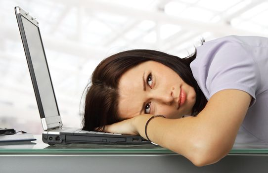 portrait of a girl resting with his head on a laptop