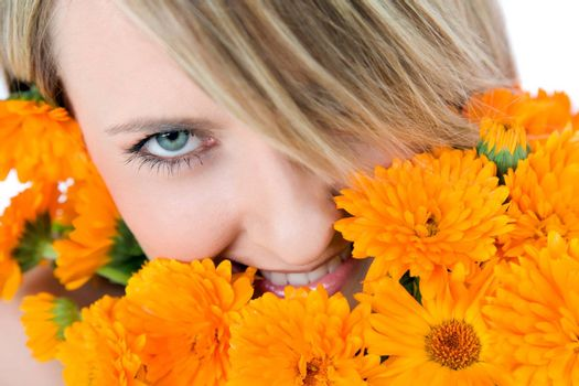Close-up of beautiful female face holding marigolds, colourfull eye looking at camera