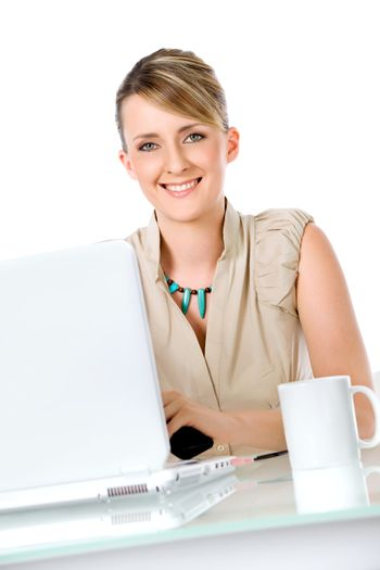 Beautiful smiling woman sitting on desk behind laptop and cup