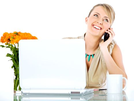 Beautiful happy female sitting behind desk with laptop, talking on the phone