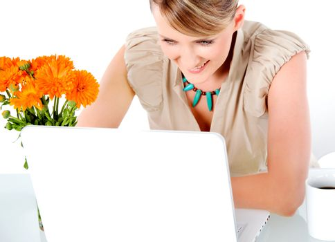 Beautiful happy woman sitting behind desk with laptop, looking at screen