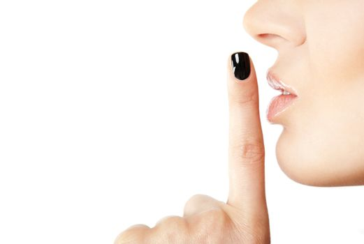 Close-up of female index finger with black fingernail put on her lips, making silence sign