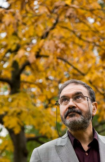 Portrait of serious adult man with glasses in park on autumn day