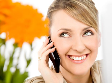 Close-up of beautiful female smiling and talking on cell phone, looking up