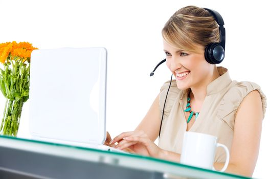 Beautiful happy female with headset sitting behind desk with laptop