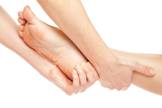 Woman hands giving a gentle foot massage isolated on white