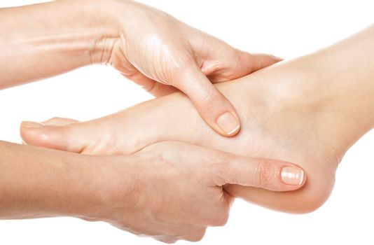 woman hands giving a foot massage on white background