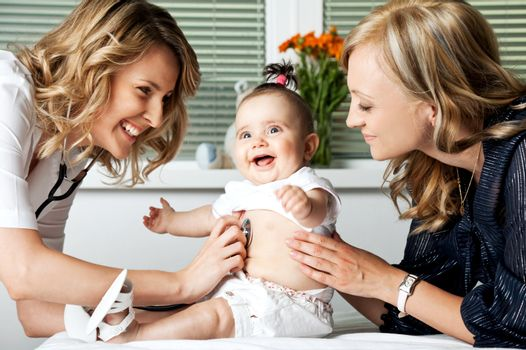 Beautiful female doctor examining little smiling baby girl, held by mother
