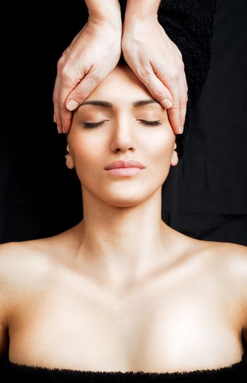 Beautiful female receiving relaxing facial massage at spa, eyes closed