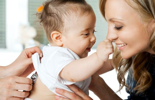Close-up of baby girl being examinated by doctor, playing with mother