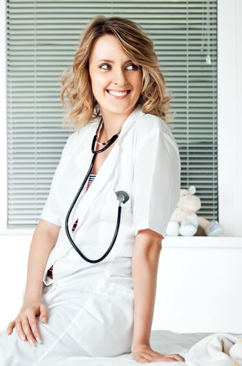 Beautiful smiling female doctor with stethoscope leaning on a couch
