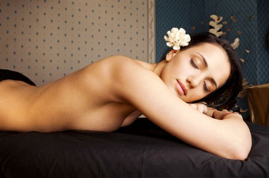 beautiful woman lying down topless and relaxing at spa studio