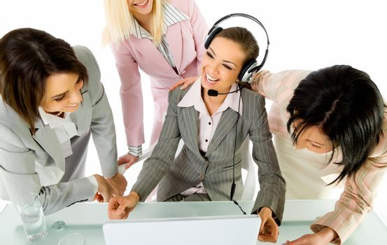 Team of four businesswomen smiling behind laptop, one with headset