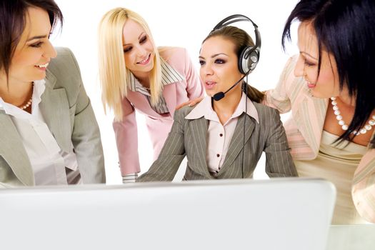 Four beautiful successful businesswomen talking behind laptop, one of them with headset