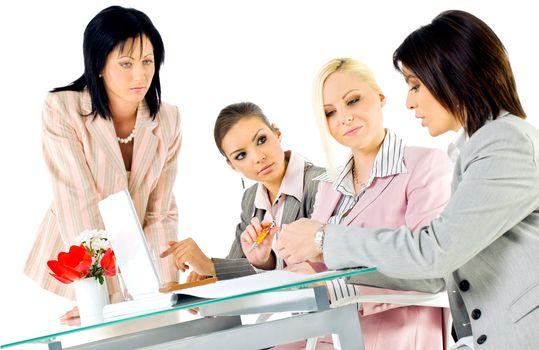 Team of four beautiful women working behind laptop
