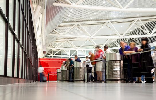 arrival section at airport with blurred figures of  waiting people