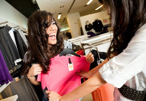 Beautiful laughing females looking at blouse in fashion store