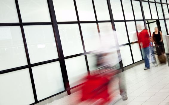 Blurred figures of people at airport, arriving with luggage