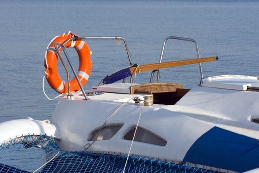 Orange lifebuoy ring on a forage of a sailing yacht