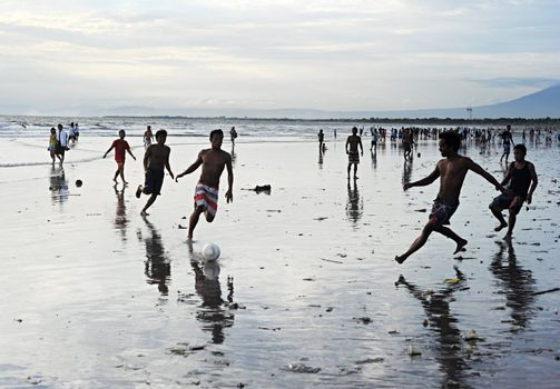 Bali, Indonesia - April 4, 2011: People plaing soccer on the  Kuta beach.Kuta's six-kilometer-long, crescent-shaped surfing beach, protected by a coral reef at its southern end, and long and wide enough for Frisbee contests and soccer games, is famous for its beautiful tropical sunsets