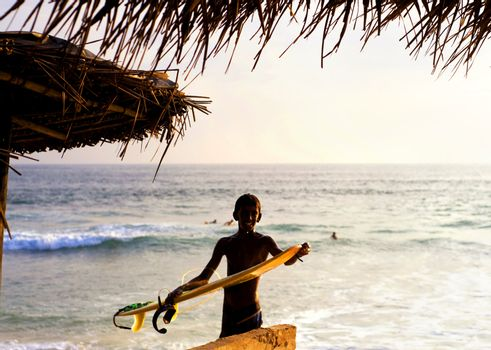 Hikkaduwa, Sri Lanka - January 23, 2011: Portrait of young local surfer with surfboard in front of the ocean