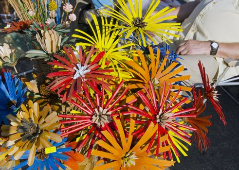 Outdoor market fair sell decorative colorful handmade artificial flowers made of natural materials cone and so on.