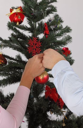 Images of a man's and a woman's hands putting together a bauble on a Christmas tree.