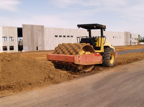 heavy duty roller  equipment by a warehouse under construction