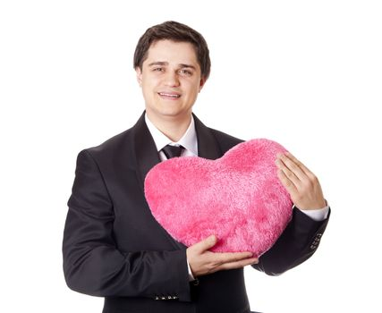 A man holding toy heart in formal black tux with tie isolated on