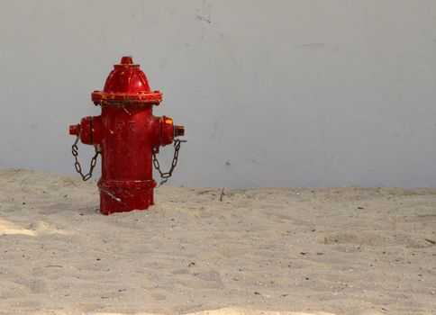 Left side view of red fire hydrant on a sandy beach