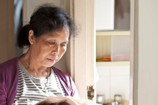 A 50s asian woman reading newspaper at home