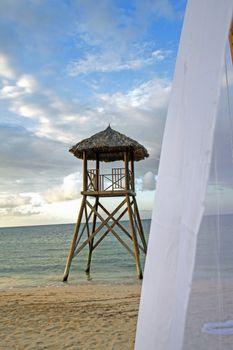Tropical watchtower overlooking a beach wedding set up