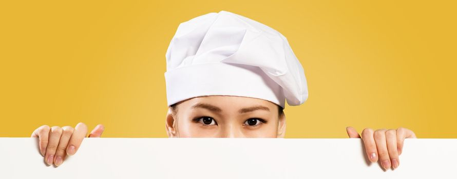 Asian female chef holding a white banner for text, hiding her face behind a poster, you can see only the eyes