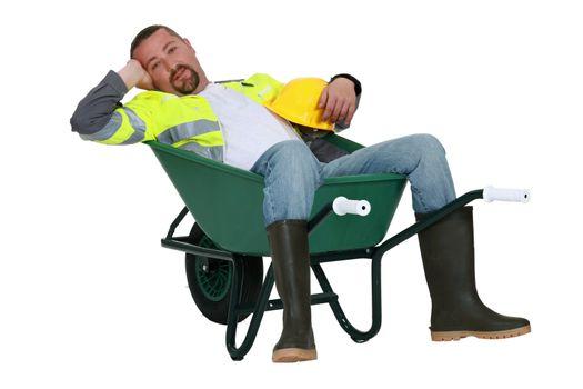 Lazy worker slumped in wheelbarrow