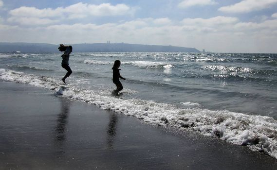 children jumping on the beach