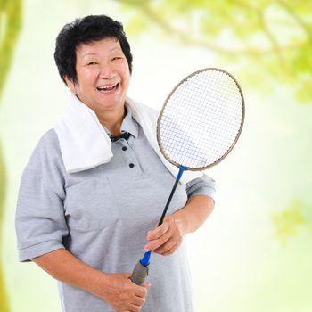Asian senior woman healthy lifestyle. Happy Asian grandparent holding badminton racket