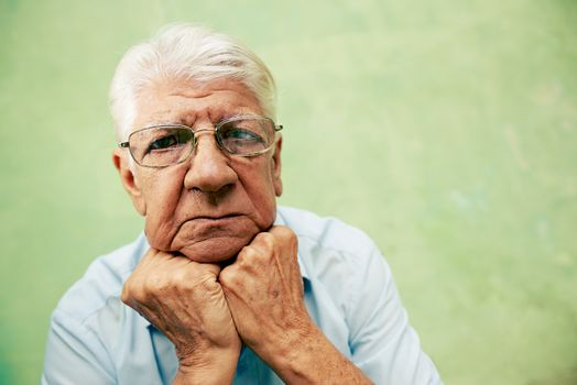 Portrait of serious old man looking at camera with hands on chin