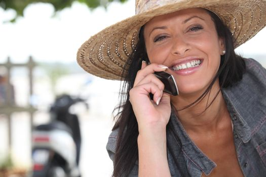 Woman wearing a straw hat talking on her mobile phone