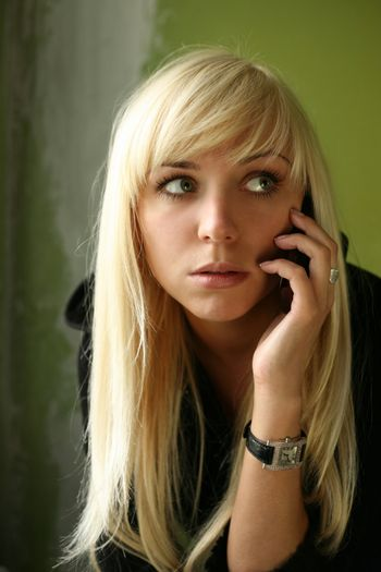 The nice blonde with the phone on a green background