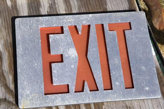 Old exit sign lying on wood.