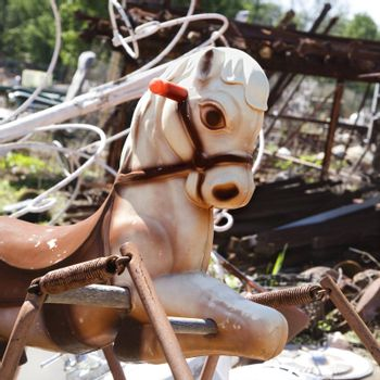 Old abandoned playground toy horse in junkyard.